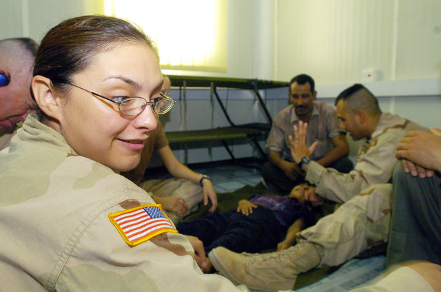PFC. Allyssa Chapoy(right)  from the 538 CSC (Combat Stress Relief) helps other soldiers from her unite adminster physical rehabilitation therapy to an Iraqi child suffering from cerebral palsy, on July 20, 2005 in Camp Echo, Iraq.(U.S. Army photo by SGT. Arthur Hamilton)(Released)