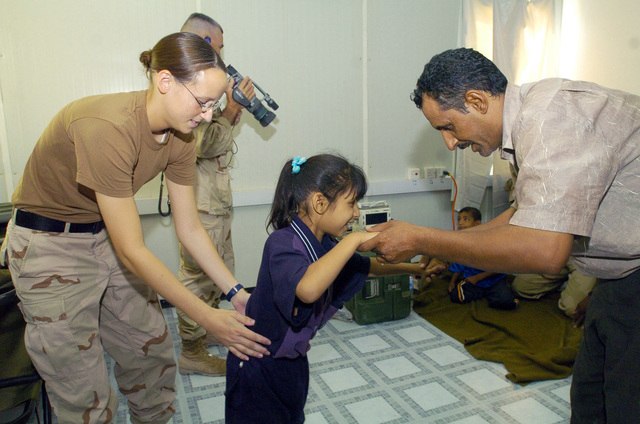 PFC. Erin Miller from the 538 CSC (Combat Stress Relief) assits an Iraqi child suffering from cerebral palsy to walk as a form of physical rehabilitation therapy, on July 20, 2005 in Camp Echo, Iraq.(U.S. Army photo by SGT. Arthur Hamilton)(Released)