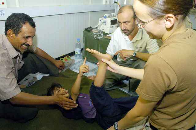 PFC. Erin Miller from the 538 CSC (Combat Stress Relief) uses hand-eye coordination exercises as a form of physical rehabilitation therapy to an Iraqi child suffering from cerebral palsy, on July 20, 2005 in Camp Echo, Iraq.(U.S. Army photo by SGT. Arthur Hamilton)(Released)