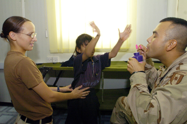 PFC. Erin Miller(left), and CAPT. Dewayne Branlett from the 538 CSC (Combat Stress Relief) use hand-eye coordination exercises as a form of physical rehabilitation therapy to an Iraqi child suffering from cerebral palsy, on July 20, 2005 in Camp Echo, Iraq.(U.S. Army photo by SGT. Arthur Hamilton)(Released)