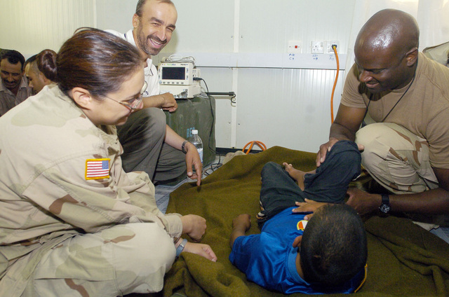 SGT. Earnesk Sharp and PFC. Allyssa Chapoy from the 538 CSC (Combat Stress Relief) use hand-eye coordination exercises as a form of physical rehabilitation therapy to an Iraqi child suffering from cerebral palsy, on July 20, 2005 in Camp Echo, Iraq.(U.S. Army photo by SGT. Arthur Hamilton)(Released)