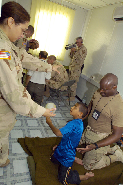 U.S. Army PFC. Allyssa Chapoy from the 538 CSC (Combat Stress Relief) uses hand-eye coordination exercises as a form of physical rehabilitation therapy to an Iraqi child suffering from cerebral palsy, on July 20, 2005 in Camp Echo, Iraq.(U.S. Army PHOTO by SGT. Arthur Hamilton) (Released)