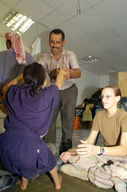 U.S. Army PFC. Erin Miller from the 538 CSC (Combat Stress Relief) adminsters physical rehabilitation therapy to an Iraqi child suffering from cerebral palsy, on July 20, 2005 in Camp Echo, Iraq.(U.S. Army PHOTO by SGT. Arthur Hamilton) (Released)