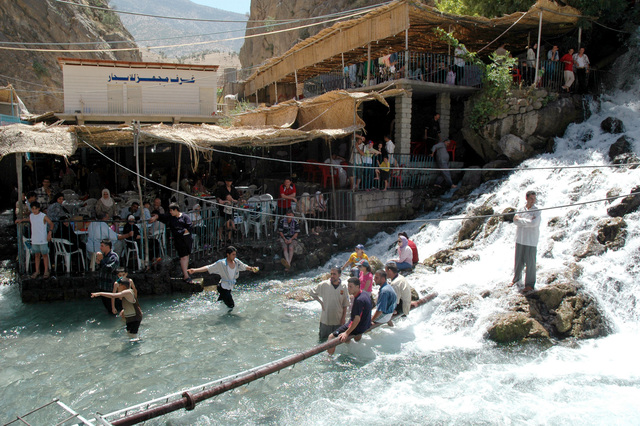 Several Iraqis cool off by standing in the water that flows from a spring-fed waterfall. This is a favorite tourist destination in the summertime and is located outside of Arbil, Arbil Province, Iraq (RQ)