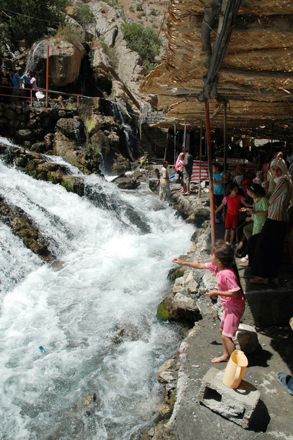 Several Iraqis stand on a walkway enjoying the coolness from the running water that flows from a spring-fed waterfall. This is a favorite tourist destination in the summertime and is located outside of Arbil, Arbil Province, Iraq (RQ)