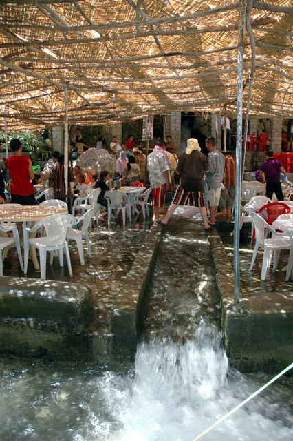 This is a covered dining area showing the water from the spring-fed waterfall running along a small canal. This is area is a favorite tourist destination during the summertime and is located outside of Arbil, Arbil Province, Iraq (IRQ)