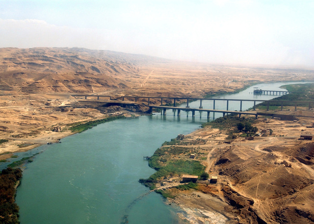 This is an aerial view of two bridges, one for vehicle traffic and the other for rail traffic, that cross the Tigris River near the Electrical Power Generation Plant, located in Bayji, Salah Ad Din Province, Iraq (IRQ), during Operation IRAQI FREEDOM