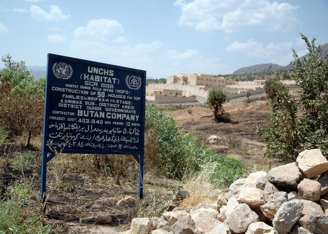 This sign commemorates the construction of 50 homes (seen in the background) by the United Nations Center for Human Settlements (UNCHS) HABITAT Habitat for Humanity Project in Brifka, Dahuk Province, Iraq (IRQ), during Operation IRAQI FREEDOM