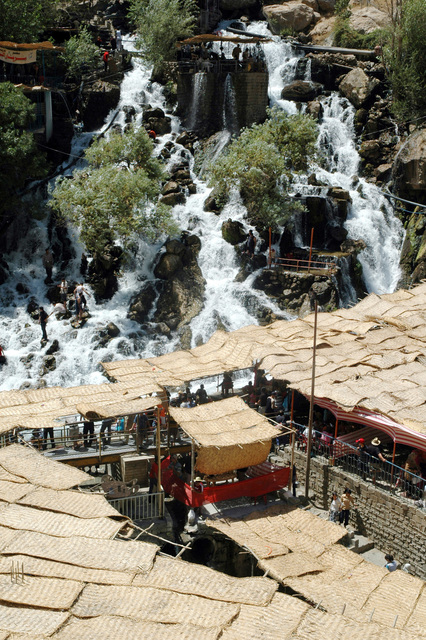 This spring-fed waterfall, located outside of Arbil, Arbil Province, Iraq (IRQ), is a favorite tourist destination during the summertime. The covered facilities are dining areas and the water from the waterfall runs along small canals through the center of each dining area