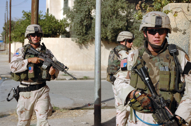 U.S. Army STAFF SGT. Benjamin G. Emery (right), SPC. Paul E.'Doc'Hendershot (center), and STAFF SGT. Kelekolio P. Paresa conduct a foot patrol through the streets of Mosul, Iraq, July 23, 2005.  The Soldiers are assigned to Weapons Squad, 3rd Platoon, Company C, 3rd Battalion, 21st Infantry Regiment, 1ST Stryker Brigade Combat Team, 25th Infantry Division, Fort Lewis, Wash.  (U.S. Army photo by SPC. Jeremy D. Crisp.)