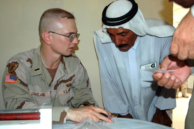 U.S. Army 1ST LT. Derek K. Loveland, fire directions officer, Battery C, 2nd Battalion, 8th Field Artillery Regiment, 1ST Stryker Brigade Combat Team, 25th Infantry Division, Fort Lewis, Wash., hands out a weapons card to an Iraqi Sheik after a security council meeting July 26, 2005, at Forward Operating Base Q-West, Iraq.  (U.S. Army photo by SPC. Jeremy D. Crisp) (Released)