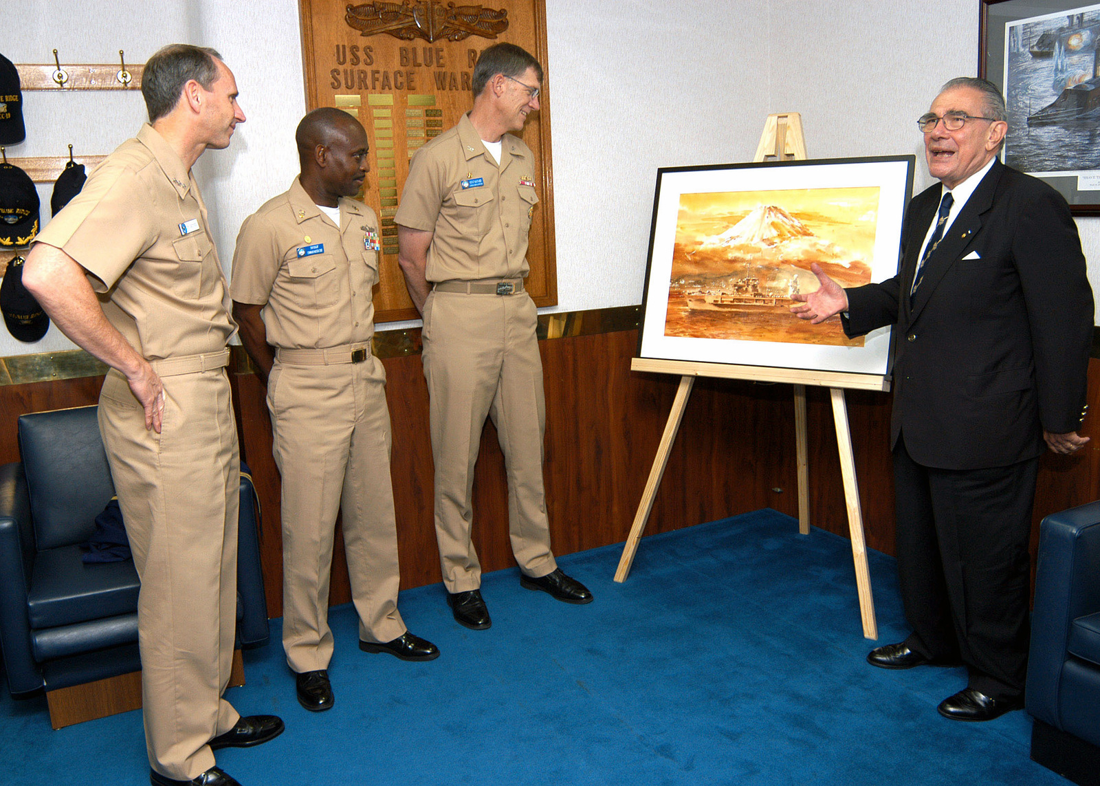 US Navy (USN) Vice Admiral (VADM) Jonathan Greenert (left), Commander, US Seventh Fleet; USS BLUE RIDGE (LCC 19) Command MASTER CHIEF (Surface Warfare) (CMDMC (SW)) Anthony E. Knight (second from left); and BLUE RIDGE Commanding Officer, Captain (CAPT) J. Stephen Maynard (center), look on as Mr. Fred Harris unveils his newest painting. Mr. Harris, president of the Navy League in Japan, presented the officers and crew of BLUE RIDGE a painting of their ship with Mt. Fuji in the background