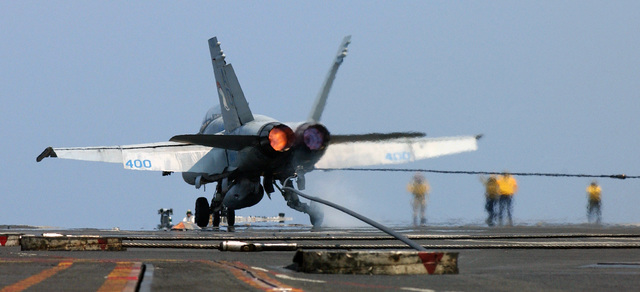 A US Navy (USN) F/A-18D Hornet, Strike Fighter Squadron 106 (VFA-106), Gladiators, Naval Air Station (NAS) Oceana, Virginia (VA), lights its afterburners to maintain full power after making a successful arrested recovery aboard the USN Nimitz Class Aircraft Carrier USS HARRY S. TRUMAN (CVN 75). The TRUMAN is conducting carrier qualifications and sustainment operations off the East Coast