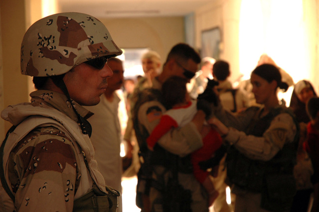 An Iraqi soldier stands guard while U.S. Soldiers from the 1ST Stryker Brigade Combat Team, 25th Infantry Division, Fort Lewis, Wash., conduct a medical screening for Iraqi children at a school house July 28, 2005, in Mosul, Iraq. (U.S. Army photo by SPC. Jeremy D. Crisp) (Released)