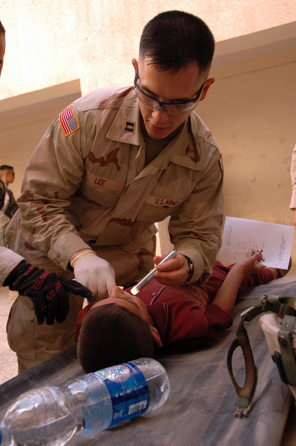 U.S. Army CAPT. Cyrus J. Lee, dentist, 1ST Stryker Brigade Combat Team, 25th Infantry Division, Fort Lewis, Wash., conducts a dental screening on an Iraqi child July 28, 2005, in Mosul, Iraq.  (U.S. Army photo by SPC. Jeremy D. Crisp) (Released)