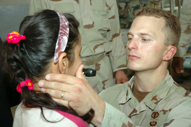 U.S. Army MAJ. David L. Brown, surgeon, 1ST Battalion, 24th Infantry Regiment, 1ST Stryker Brigade Combat Team, 25th Infantry Division, Fort Lewis, Wash., checks an Iraqi girl's throat for infection during a medical screening July 28, 2005, in Mosul, Iraq.  (U.S. Army photo by SPC. Jeremy D. Crisp) (Released)