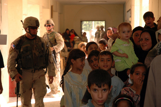 U.S. Army Soldiers from the 1ST Stryker Brigade Combat Team, 25th Infantry Divison, Fort Lewis, Wash., assist Iraqi families during a medical screening July 28, 2005, in Mosul Iraq.  (U.S. Army photo by SPC. Jeremy D. Crisp) (Released)