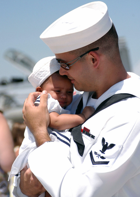 A US Navy (USN) PETTY Officer Third Class (PO3) Aviation Structural Mechanic (AM) hold his child for the first time after returning from a six-month deployment aboard the USN Nimitz Class Aircraft Carrier USS CARL VINSON (CVN 70) [not shown] in support of the global war on terrorism (GWOT)
