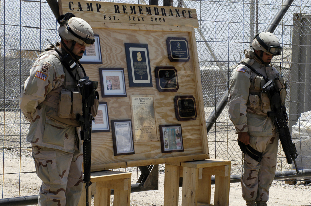 U.S. Army CHIEF Warrant Officer Jose Soto and STAFF SGT. George Mauras from the 306th Military Police Battalion bow their heads for prayer during a dedication ceremony for a new detainee compound at Abu Ghraib prison Sunday. The compound is dedicated to the memory of the N.Y. police officers and firefighters who perished on Sept. 11, 2001 in the World Trade Center tragedy. (U.S. Army photo by SGT. Lynne Steely) (Released)