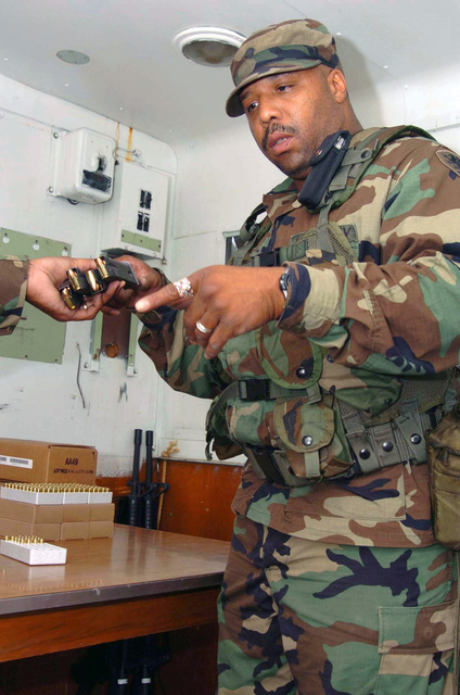 Michigan Army National Guard (MIARNG) SPECIALIST (SPC) Demille OConnor, a Healthcare SPECIALIST from the State Medical Command in Detroit, Michigan (MI), distributes 9 mm ammunition at a pistol range during his annual qualification training