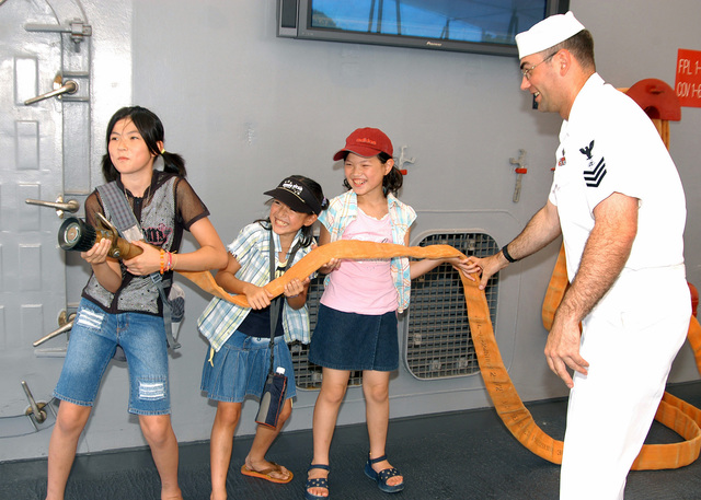 US Navy (USN) Electronics Technician First Class (ET1) Tyrone A. Gideon shows Japanese children the proper way to handle a fire hose during their tour of the main deck of the Amphibious Command Ship USS BLUE RIDGE (LCC 19). Approximately 10,000 Japanese citizens toured the 7th Fleet command ship during Friendship Day, an annual Open House event held on board Fleet Activities Yokosuka to honor the friendly relationship between the local Navy and Japanese communities