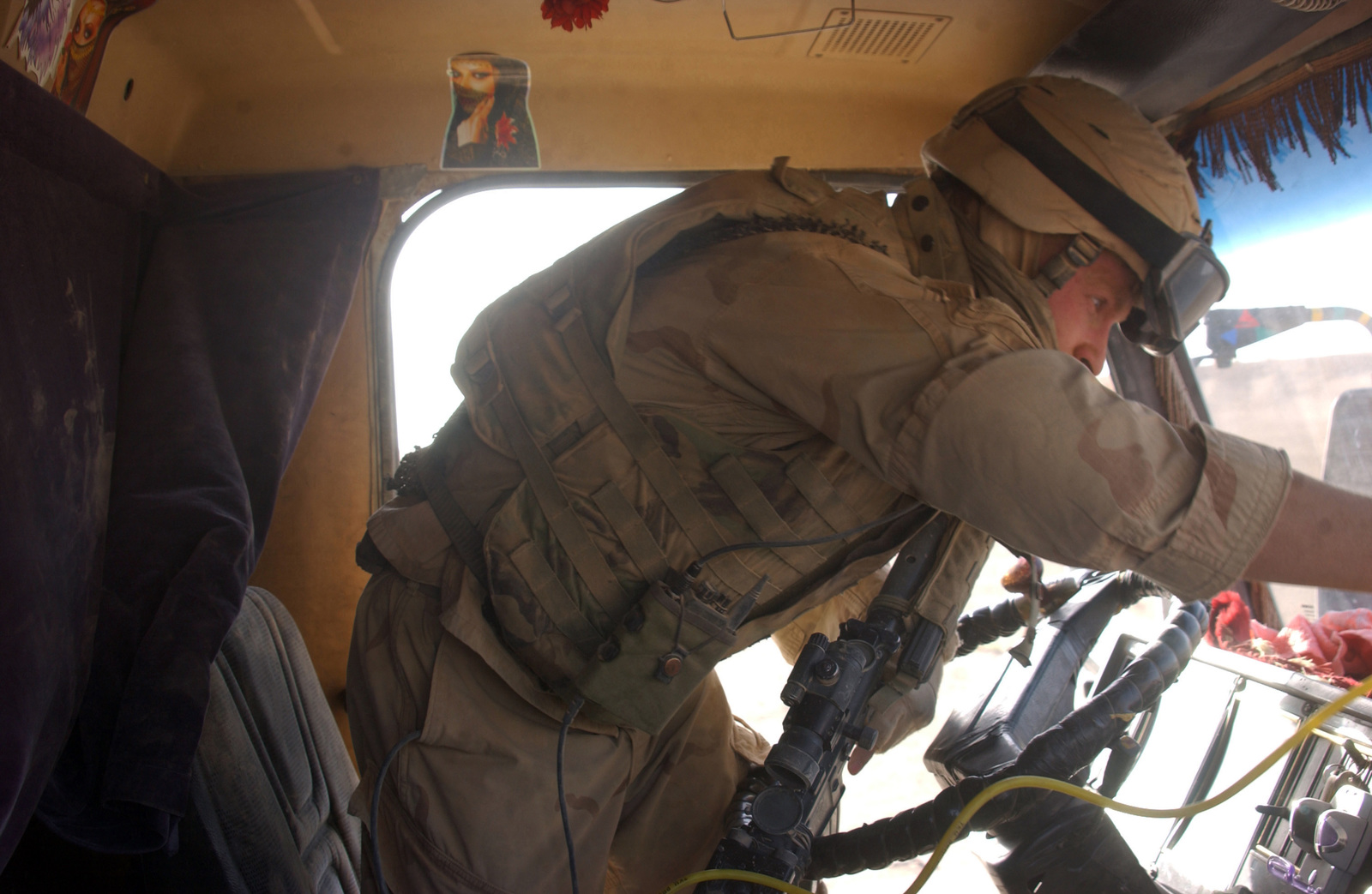 U.S. Army STAFF SGT. John Blair, with 2nd Squadron, 14th Cavalry (2-14), searches a vehicle for weapons or other contraband during a patrol near the Syrian border on Aug. 10, 2005.  2-14, operating out of Combat Outpost Rawah, is currently in the area to suppress terrorists from crossing the Syrian border into Iraq.  (U.S. Army photo by STAFF SGT. Kyle Davis)  (Released)