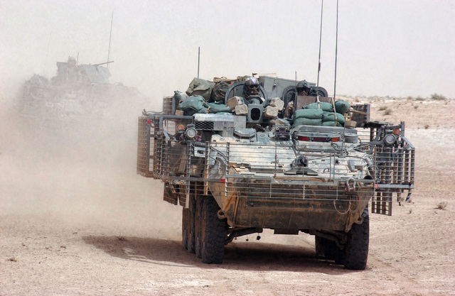 US Army (USA) Soldiers with 2nd Squadron (SQD), 14th Cavalry Regiment (CAV REGT) (2-14), Fort Lewis, Washington (WA), travel through the desert in their M1126 Stryker Infantry Carrier Vehicle (ICV) with Slat Armor cage on patrol near the Syrian border. The 2-14 is operating out of Combat Outpost (COP) Rawah, to keep terrorists from crossing the Syrian border into Iraq during Operation IRAQI FREEDOM