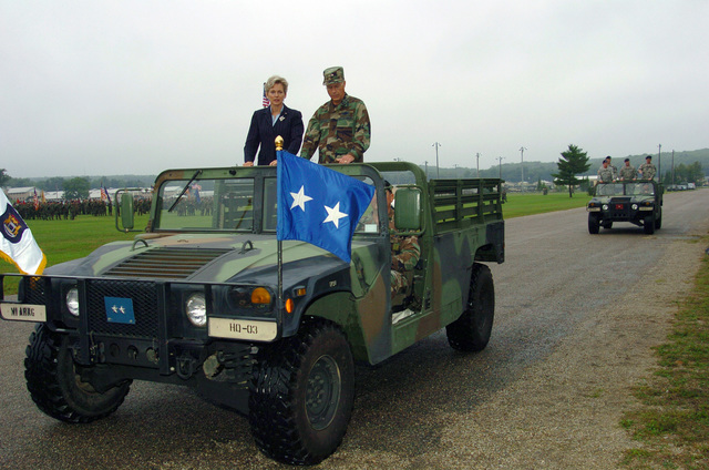 Michigan (MI) Governor Jennifer Granholm and Michigan Army National Guard (MIARNG) Major General (MGEN) Thomas Cutler, review the troops from an open High Mobility Multipurpose Wheeled Vehicle (HMMWV) at the MIARNG Annual Training Parade marking the end of the 2005 Annual Training Exercise (ATE) at Camp Grayling, Michigan. (A3596)