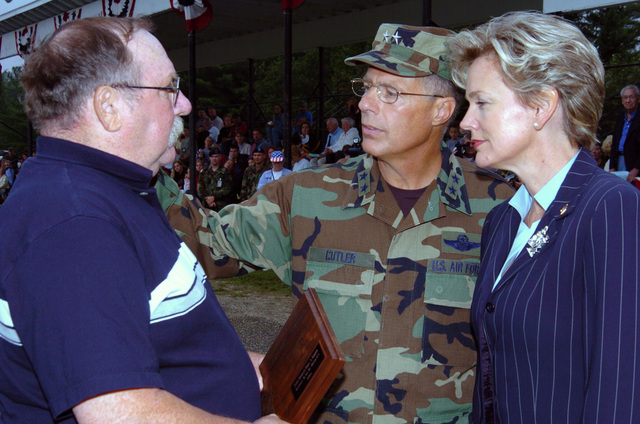 Mr. Rick Kieffer, left, father of STAFF Sergeant (SSG) Rick Kieffer, from the Detroit, Michigan (MI), Security Force Battery (SFB) receives a plaque from Michigan Governor Jennifer Granholm, right and Michigan Army National Guard (MIARNG) Major General (MGEN) Thomas Cutler, during a ceremony at the Annual Training Parade marking the end of the 2005 Annual Training Exercise (ATE) at Camp Grayling, Michigan. SSG Kieffer died March 15, 2005 in Baghdad, Iraq, when enemy forces using small arms fire attacked his unit. (A3596)