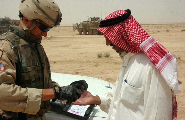 U.S. Army SPC. Alban Norton, from C Troop, with 2nd Squadron, 14th Cavalry (2-14), uses Exspray on an Iraqi man to determine if the man has handled explosives recently, during a patrol near the Syrian border on Aug. 10, 2005.  2-14, operating out of Combat Outpost Rawah, is currently in the area to suppress terrorists from crossing the Syrian border into Iraq.  (U.S. Army photo by STAFF SGT. Kyle Davis)  (Released)