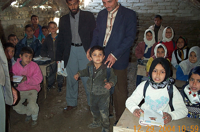 Photograph of Iraqi school children and their teachers in an unheated rural school in northern Iraq during Operation IRAQI FREEDOM