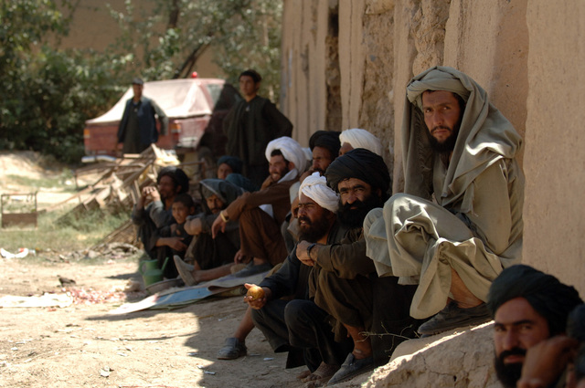 A group of Afghan locals listen to the loud speaker that was place outside a shura meeting held at Baghran Valley between local leaders and American officers on August 22, 2005. Shura meetings are going on everywhere in Afghanistan to encourage people to vote on the incoming parliamentary elections on September 18, 2005. (U.S. Army PHOTO by PFC. Leslie Angulo) (Released)