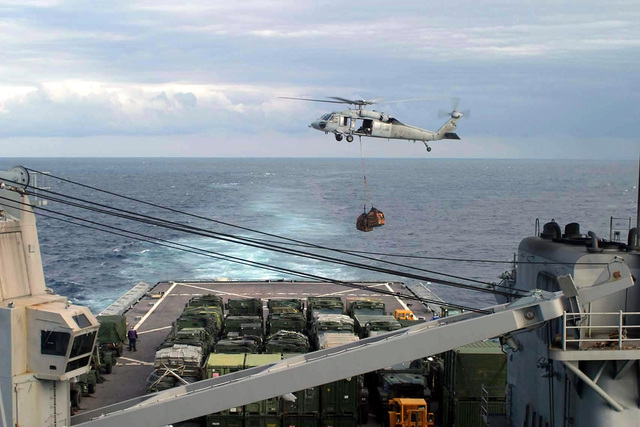 A US Navy (USN) Sikorsky MH-60S Seahawk helicopter, Helicopter Sea Combat Squadron 28 (HCS-28), delivers supplies to the USN Whidbey Island Class Dock Landing Ship USS CARTER HILL (LSD 50) during a Vertical Replenishment (VERTREP) at sea while the USS CARTER HILL is steaming across the Atlantic Ocean and participating in an underway-training exercise with the USS NASSAU Expeditionary Strike Group (ESG). (SUBSTANDARD)