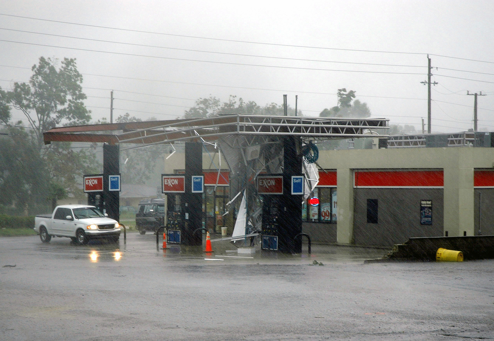 An Exxon gas station remains open despite losing its roof