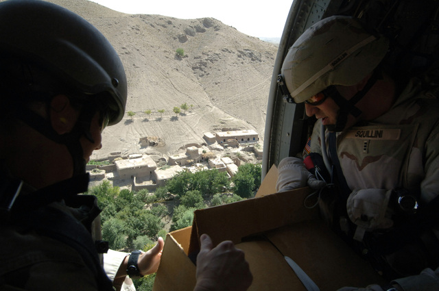 SGT. 1ST Class Jill Chalfant (left) from 362nd Battalion PSYOP (Psychological Operations) and CHIEF Warrant Officer 3 Michael Squillini from 173rd Airborne Brigade, drop leaflets from a Black Hawk Helicopter near the villages of Shirin and Adam Khan in Afghanistan, August 29, 2005. Because of the upcoming parliamentary elections, leaflet drops have been a very resourceful method to promote messages of no fighting and support to the government of Afghanistan. (U.S. Army PHOTO by PFC. Leslie Angulo) (Released)