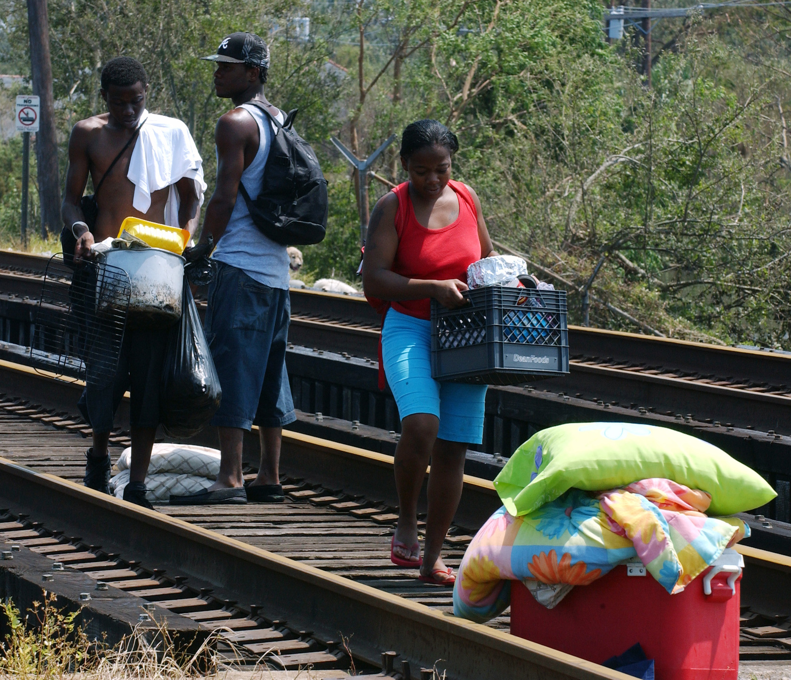 [Hurricane Katrina] New Orleans, LA, August 31, 2005 -- Local residents carry personal items over dry land to reach a second boat which will bring them to dry land.  They were brought to this location via FEMA Urban Search and Rescue personnel and local rescue workers.  Photo by Jocelyn Augustino/FEMA