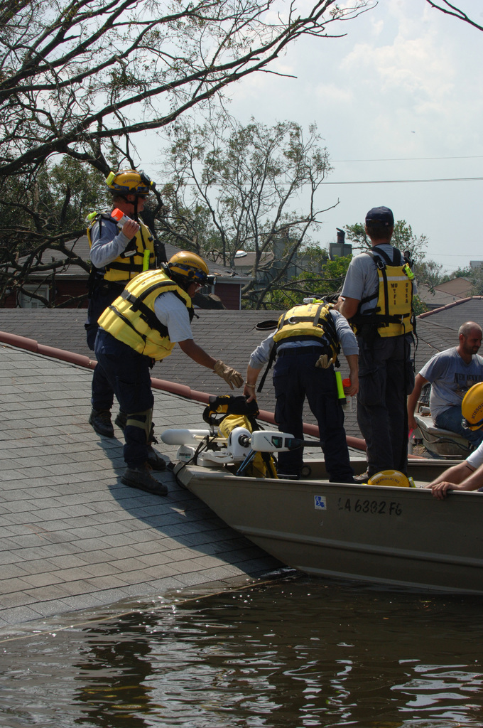 [Hurricane Katrina] New Orleans, LA, August 31, 2005 - A FEMA Urban Search and Rescue (US&R)team from Missouri Task Force 1 moves equipment out of a boat onto a roof as they prepare to search this attic for survivors and the deceased. New Orleans is flooded and is being evacuated as a result of Hurricane Katrina. Photo by Jocelyn Augustino/FEMA