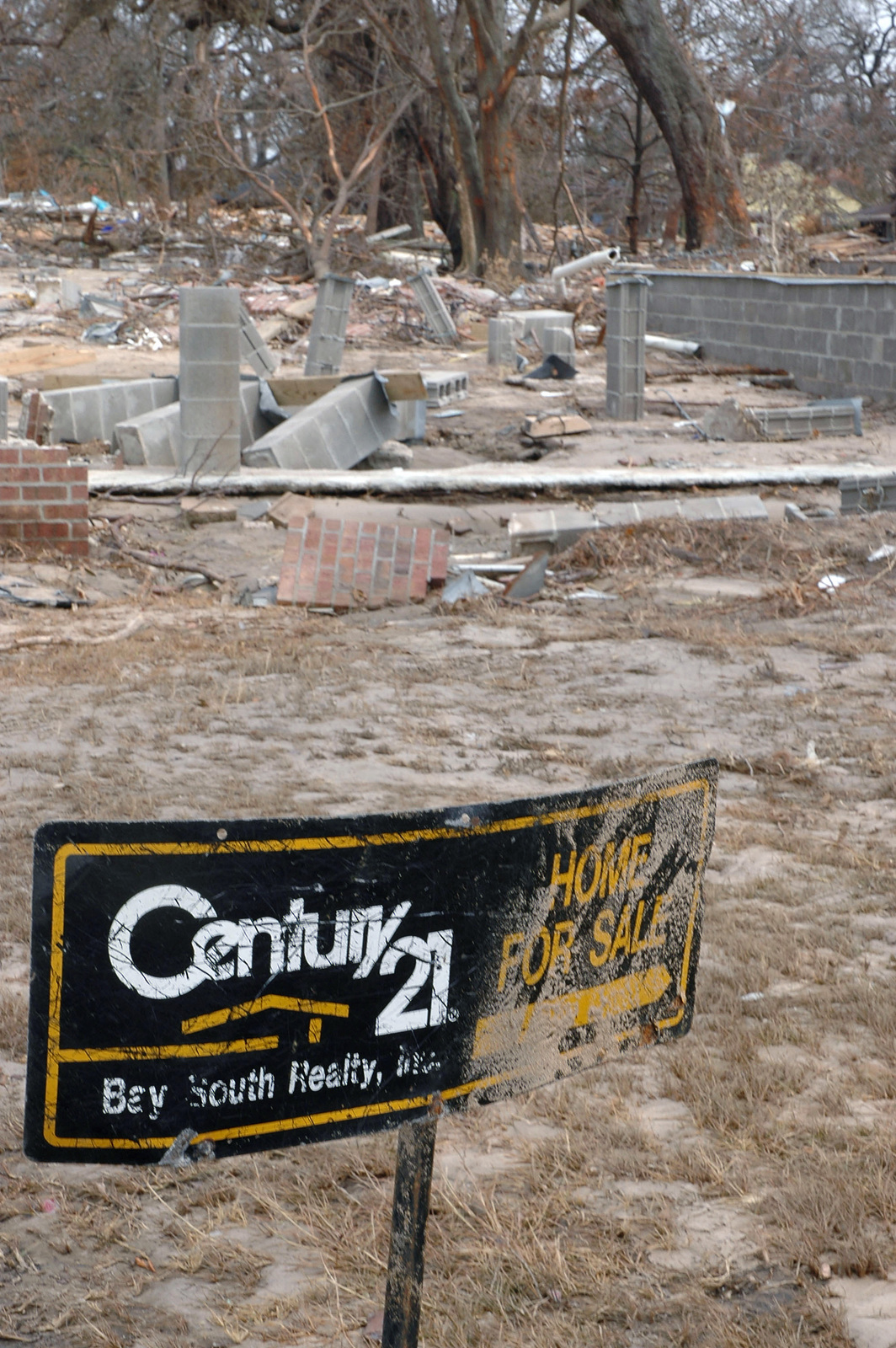 A home for sale sign stands in front of the scattered debris that
