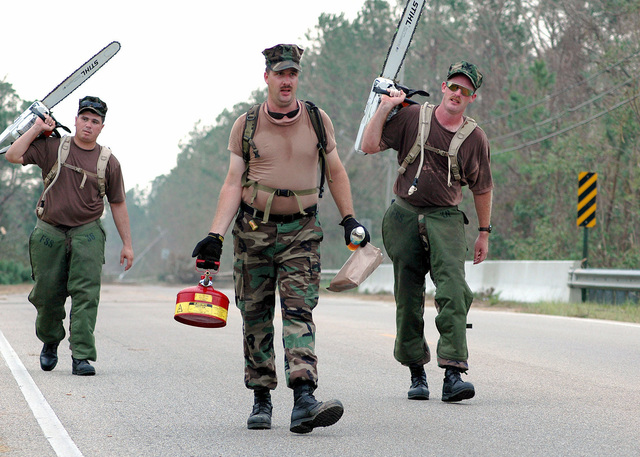 US Navy Seabees, Equipment Operator First Class (EO1) Jonathan Burleson (left), EO1 Eric Koppel and Equipment Operator Second Class (EO2) Robert Embery (right), head out with chainsaws and gasoline to the next set of tree limbs blocking a roadway in Gulf, Mississippi (MS). The Navy's involvement in the Hurricane Katrina Humanitarian Assistance Operations is led by the Federal Emergency Management Agency (FEMA), in conjunction with the Department of Defense (DoD)