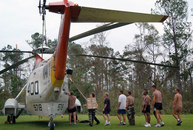 US Navy (USN) Sailors and civilian personnel unload food and water from a USN UH-3H Sea King helicopter, brought in from Naval Air Station (NAS) Pensacola, Florida (FL), providing support and relief to victims of Hurricane Katrina at the Stennis Space Center (SSC), Mississippi (MS). The space center is being used as an evacuation center for hurricane refugees