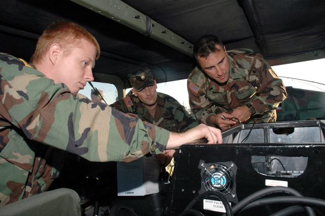 Ohio Army National Guard (OHARNG) Private First Class (PFC) Swonger (left), Major (MAJ) Nagy (center), and Lieutenant (LT) Luca (right) prepare the communications system in the Commanders vehicle in preparation for traveling with several companies of OHARNG Military Police (MP) Companies that are going to depart in a convoy from the Army enclave at Rickenbacker Air National Guard Base (ANGB), Ohio (OH), to Fort Shelby, Mississippi (MS), to be assigned duties as part of Joint Task Force (JTF) Katrina in support of Hurricane Katrina relief operations