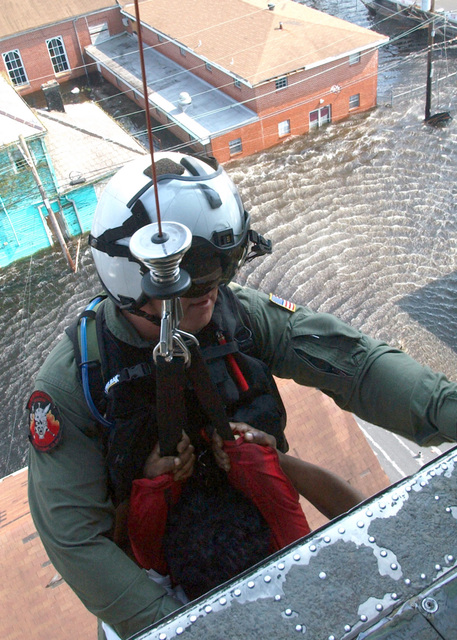 US Navy (USN) Search and Rescue (SAR) Swimmer Aviation Warfare Systems Operator 1ST Class (AW1) Tim Hawkins prepares to bring a Hurricane Katrina victim onboard a USN Sikorsky Sh-60B Seahawk Helicopter that he has just rescued from a building rooftop in downtown New Orleans, Louisiana (LA). AW1 Hawkins is part of the US Navys contribution to the humanitarian assistance operation, led by the Federal Emergency Management Agency (FEMA) and working in conjunction with the Department of Defense (DoD), that is delivering humanitarian and relief assistance to the Gulf Coast victims of Hurricane Katrina