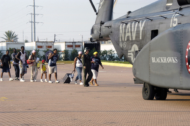 US Navy (USN) PETTY Officer Second Class (PO2) Kirk Crabb, Aviation Machinist's Mate, Helicopter Mine Countermeasures Squadron 15 (HM-15), Naval Air Station (NAS) Corpus Christi, Texas (TX), directs Hurricane Katrina evacuees toward the rear ramp of a USN MH-53E Sea Dragon helicopter at the Ernest N. Morial Convention Center parking lot in New Orleans, Louisiana (LA). The Navy's involvement in the Hurricane Katrina Humanitarian Assistance Operations is led by the Federal Emergency Management Agency (FEMA), in conjunction with the Department of Defense (DoD)