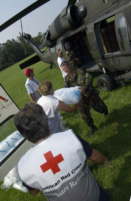 US Army (USA) National Guard (ANG) personnel from Mobile, Alabama (AL), American Red Cross volunteers and displaced citizens unload bags of ice from a USA UH-60 Black Hawk helicopter in support of the Hurricane Katrina relief effort
