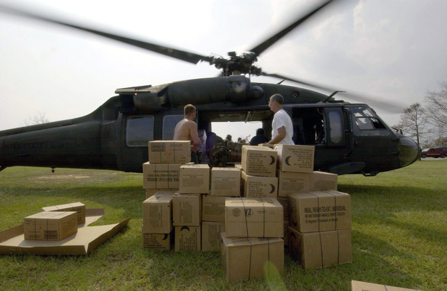 US Army (USA) National Guard (ANG) personnel from Mobile, Alabama (AL), American Red Cross volunteers and displaced citizens unload boxes of Meals Ready to Eat (MRE) from a USA UH-60 Black Hawk helicopter in support of the Hurricane Katrina relief effort