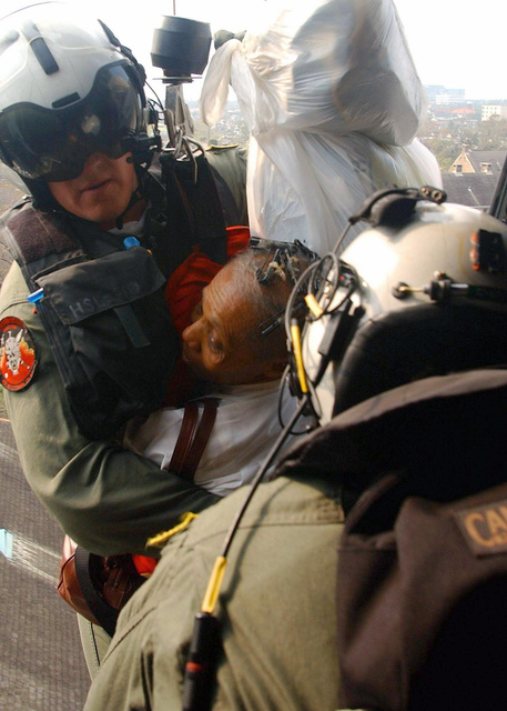 US Navy (USN) PETTY Officer First Class (PO1) Tim Hawkins, Search and Rescue (SAR) Swimmer, and a Hurricane Katrina survivor, along with some of her belongings, are hoisted onboard a USN SH-60B Seahawk helicopter. The Navy is contributing to the humanitarian assistance operations led by the Federal Emergency Management Agency (FEMA) in conjunction with the Department of Defense (DoD)
