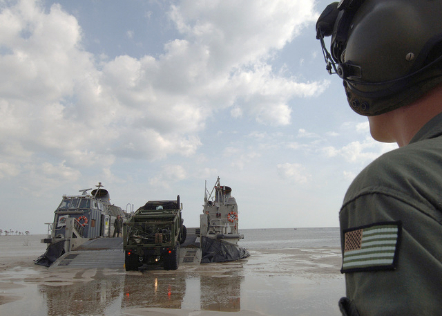 A US Marine Corps (USMC) MK-23 Medium Tactical Vehicle Replacement (MTVR) 7-ton cargo truck offloads from a Landing Craft Air-Cushion (LCAC) craft form Assault Craft Unit Four (ACU-4) after arriving on the beach to begin clean operations in Biloxi, Mississippi (MS), during Hurricane Katrina relief operations. The USN and USMC are taking part in Joint Task Force (JTF) Katrina, by aiding in humanitarian assistance operations, led by the Federal Emergency Management Agency (FEMA), in conjunction with the Department of Defense (DOD)
