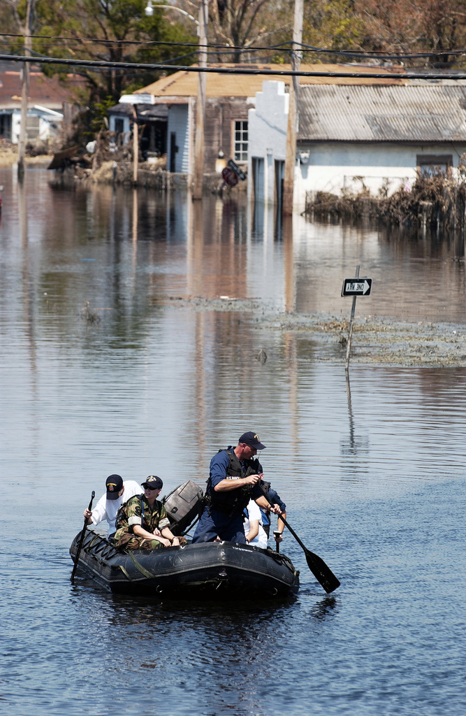 """US Navy (USN) Sailors use a """"Zodiac"""" Combat Rubber Reconnaissance Raft to ferry evacuees to safety, during Search And Rescue (SAR) operations in the flooded city of New Orleans, Louisiana (LA), during Hurricane Katrina relief operations. The USN is taking part in Joint Task Force (JTF) Katrina, by aiding in humanitarian assistance operations, led by the Federal Emergency Management Agency (FEMA), in conjunction with the Department of Defense (DOD)"""