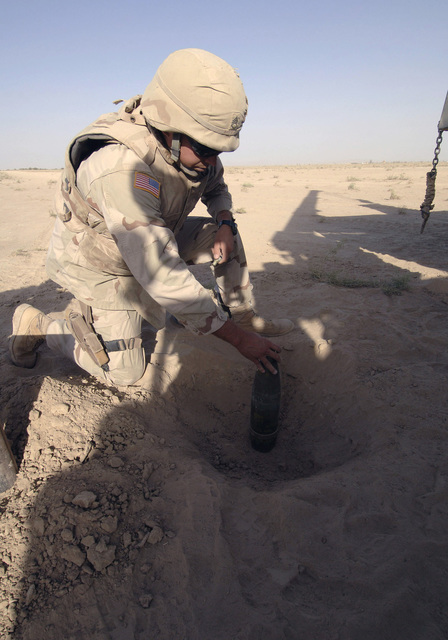 US Army (USA) STAFF Sergeant (SSG) Adam Whitman, 789th Explosive Ordnance Disposal (EOD) Company, Georgia Army National Guard (GAARNG), partially buries a 105mm Mortar Projectile during a metal armor ballistics resistance test demonstration for military vehicles floor plating at Kandahar Airfield, Afghanistan, during Operation ENDURING FREEDOM. (A3588)