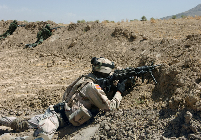 A US Army (USA) Soldier armed with an FNMI 5.56 mm M249 Squad Automatic Weapon (SAW) and in full desert gear, from the Combined Joint Task Force 76 (CJTF76) Quick Reaction Force (QRF) takes aim. His mission is part of an exercise in conjuction with their International Security Assistance Force (ISAF) counterparts, in support of Operation ENDURING FREEDOM